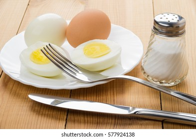 Boiled full eggs and half of eggs in white plate, salt, fork and knife on wooden table