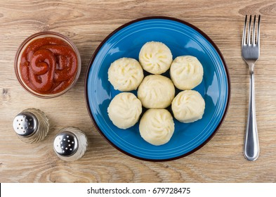 Boiled khinkali in blue plate, pepper, salt, ketchup and fork on wooden table. Top view