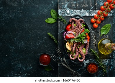 Boiled large octopus with grilled vegetables in a black stone plate. Seafood. Top view. Free space for your text.