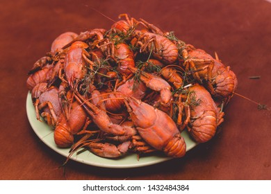 Boiled large red river crayfish on a green plate on a brown table background.Crayfish on the table.