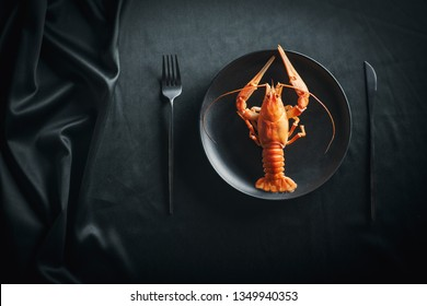 Boiled lobster in a black plate on a black background, top view. Boiled big red fresh crawfish in black plate with black tableware
