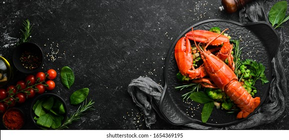 Boiled lobster with vegetables on a black stone plate. Seafood. Top view. Free space for your text.