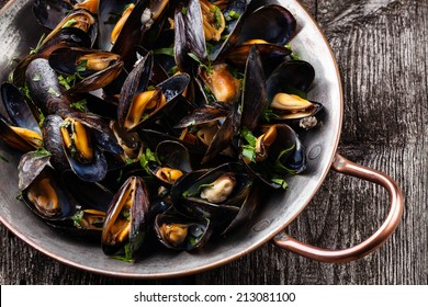 Boiled mussels in copper cooking dish on dark wooden background close up