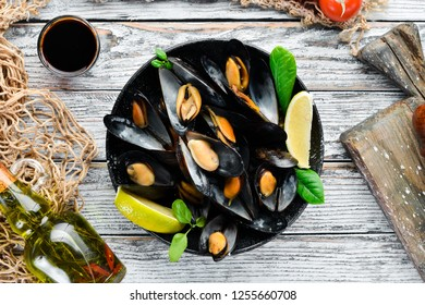 Boiled mussels with spices in a plate. Top view. Free space for your text. On the old background.