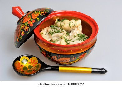 Boiled pelmeni in khokhloma painted russian wooden dishes with spoon on gray