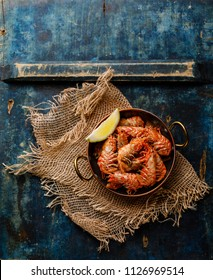 Boiled pink Greenland Prawn Shrimp in copper pan on blue background