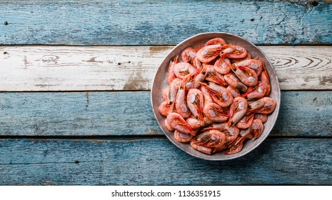 Boiled pink Prawn Shrimp in bowl on wooden background copy space