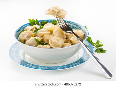 Boiled prepared homemade russian dumplings or pelmeni on the patterned plate with a fork, fresh parsley and butter on a white background
