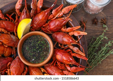 Boiled, red, delicious crayfish. Seafood with sauce. Crayfish claws in a plate