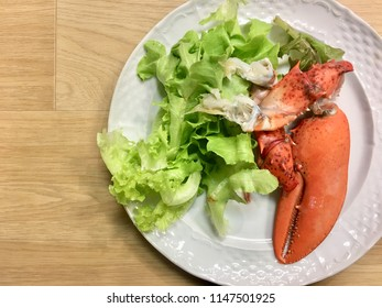 Boiled red lobster claw seafood with green vegrtable salad homemade food