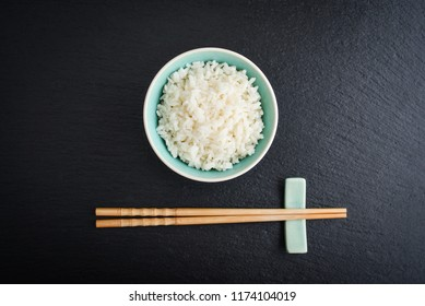 Boiled rice in bowl and  bamboo chopsticks on black slate background, top view