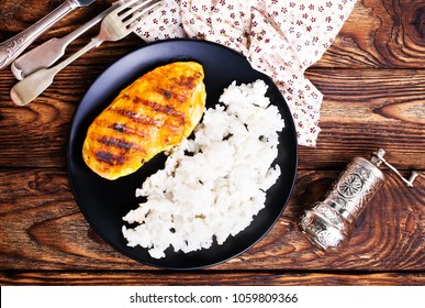 boiled rice with chicken breast on plate on a table