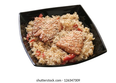 boiled rice with paprika and salmon in a black dish