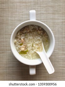 Boiled rice with pork in a cup with spoon