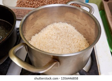 boiled rice in a stainless steel pan on a gas stove. cooking rice dishes. homemade vegetarian food