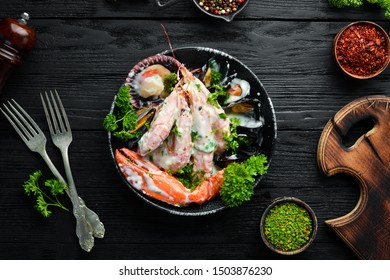 Boiled Seafood in a creamy sauce on a black stone plate. Seafood, prawns, shellfish, lobster. Top view. Free copy space.