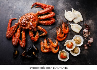 Boiled Seafood - King Crab, Prawn Shrimp, Mussels Clams, Scallops in shells, Octopus mini, Squid on Grill on dark background