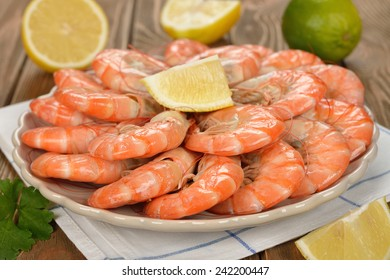 Boiled shrimp with lemon on a brown background, close-up
