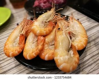 Boiled shrimp on black plate.
