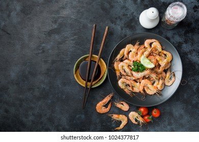 Boiled shrimps in black dish with sauce on black table.