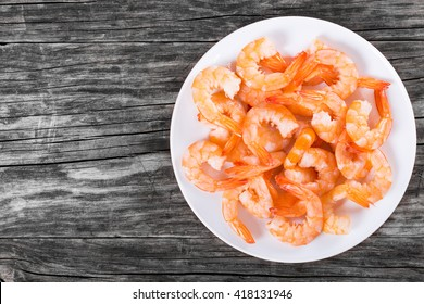 boiled tails of king shrimps on a white dish on an old rustic table, blank space left, top view