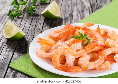 boiled tails of king shrimps on a white dish with parsley and slices of lime on an old rustic table, close-up