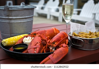 Boiled twin lobster with drawn butter, coleslaw, corn on the cob and French fries, a traditional meal of vacationers in the Coastal Maine. Summer in New England.