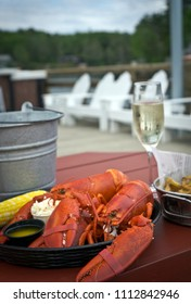 Boiled twin lobster with drawn butter, coleslaw, corn on the cob and French fries - a traditional meal of the Coastal Maine. Summer in New England.