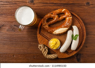 Boiled white sausages, served with beer and pretzels. Perfect for Octoberfest. Natural wooden background. Top view.