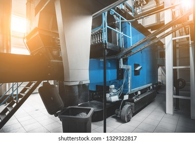 boiler room with solid wood fuel chip boiler. Blue toning with sunflare