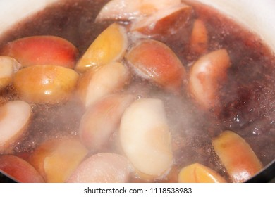 Boiling compote cooked in a pot of apples and black currant. background food and drink