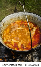boiling, hot hungarian soup with pork meat, pigs feet, potatoes, onion, is a very traditional dish of hungarian cuisine on open fire