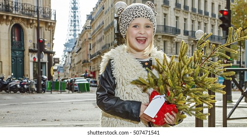 Boiling hot trendy winter in Paris. Full length portrait of smiling modern child with Christmas tree in Paris, France