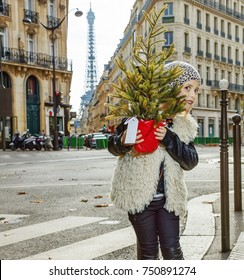 Boiling hot trendy winter in Paris. Full length portrait of trendy girl in Paris, France looking out from Christmas tree