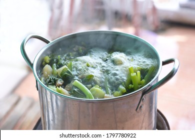 A boiling pot of vegetable soup on top of the stove.