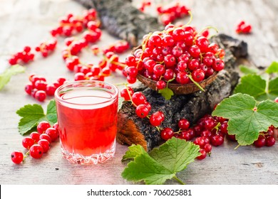 Boiling red currant drink in a glass and berries in a bowl on a tree bark