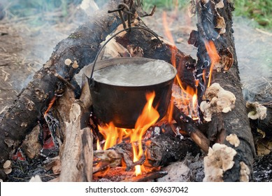 Boiling water in the bowler on the bonfire.