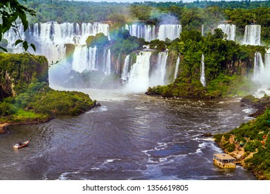 Boiling water creates a watery dust and a rainbow. Several waterfalls from Iguazu Falls. The concept of exotic and extreme tourism