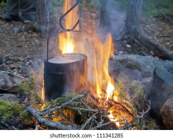 Boiling water in a kettle on fire. Set for a survival in the wood