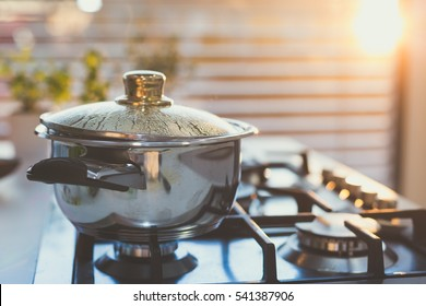 Boiling water in the pot on the stove in the evening