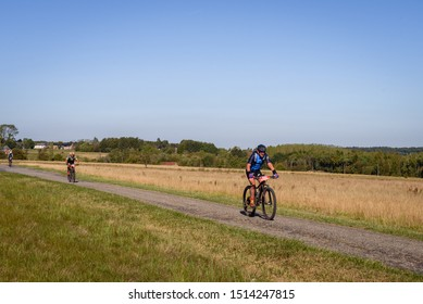 BOIS DE VILLERS, BELGIUM. Sept. 21, 2019. Mountain bike race with three men racing with bikes on field countryside road part of the Ultra Raid des trois vallees. Ardennes region, Wallonia, Belgium.