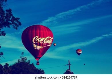 Boise, ID - September 6, 2015: a Coca Cola hot air balloon flies over a Boise neighborhood with a toned instagram filter. The balloon is one of many participants in the annual Spirit of Boise festival
