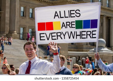 BOISE, IDAHO - JUNE 17, 2017:Man waves in front of a allies are everywhere sign