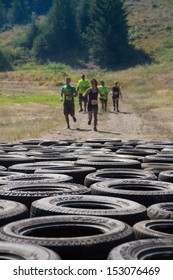 BOISE, IDAHO/USA - AUGUST 10: Group of runners race to the tire course at the The Dirty Dash in Boise, Idaho on August 10, 2013. Focus is shallow and set on the tires