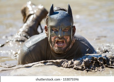 BOISE, IDAHO/USA - AUGUST 10: Runner dressed as batman swims in the mud during the The Dirty Dash in Boise, Idaho on August 10, 2013