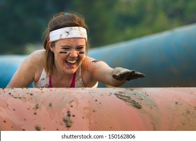 BOISE, IDAHO/USA - AUGUST 10: Unidentified woman climbs over an obstacle at the The Dirty Dash in Boise, Idaho on August 10, 2013