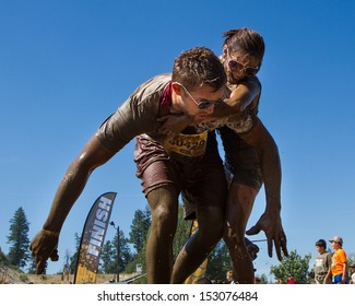 BOISE, IDAHO/USA - AUGUST 10: Unidentified woman is getting off the back of runner 40429 at the The Dirty Dash in Boise, Idaho on August 10, 2013