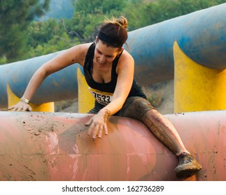 BOISE, IDAHO/USA - AUGUST 10: Woman 7533 climbs over an obstacle at the The Dirty Dash in Boise, Idaho on August 10, 2013