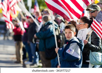 BOISE, IDAHO/USA - NOVEMBER 21, 2015: Child holding up an American Flag at the counter protest to the refugee situation in America