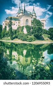 Bojnice castle is mirrored in water, Slovak republic. Cultural heritage. Travel destination. Analog photo filter with scratches.